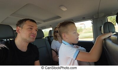 Parents with two kids having car journey - Dad, mom, son and...
