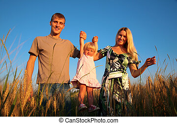 Paretns hold daughter from hands on wheat field