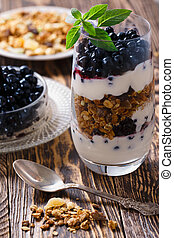 Parfait-style healthy layered breakfast with yougurt, fresh blueberries, muesli or granola in clear glass on wooden table