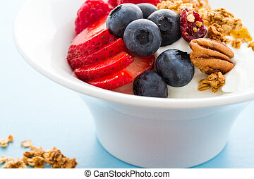 Parfait with fresh fruits and granola in white bowl.