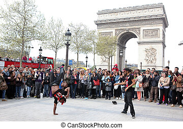 PARIS - APRIL 27:: B-boy doing some breakdance moves in front a street crowd, at Arch of Triumph, April 27 2013, Paris, France