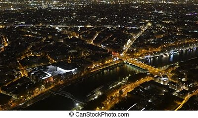 Paris at night from the Eiffel Tower. Golden embankments of the Seine look fine.