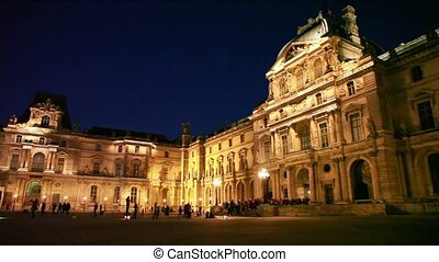Tourists walk on square in front of Louvre