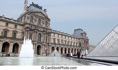 Tourists walk near fountain in front of Louvre