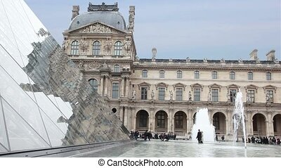 Tourists walk near fountains in front of Louvre