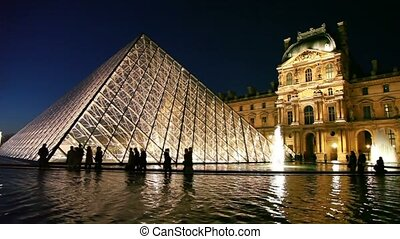 PARIS - DECEMBER 31: Tourists walk near piramid in front of Louvre in night, December 31, 2009 in Paris, France. Louvre one of world's largest museums, the most visited art museum in world and historic monument.