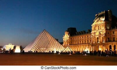 Tourists walk on square in front of Louvre in night
