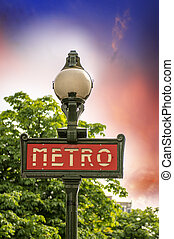 Paris, France. Classic Metro symbol. Subway sign with trees in background.