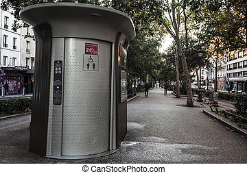 PARIS, FRANCE - OCTOBER 6, 2016: People walk by public toilet facilities onMontmartre area. More than 400 public toilet facilities scattered about the city.