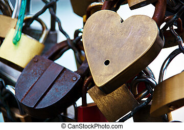 on a bridge over the seine in paris, france. couples prove their love by ewgie padlocks, they hang on the bridge railing.