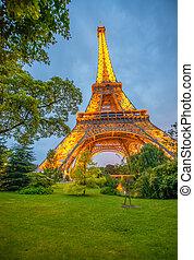 PARIS - JUNE 22, 2014: The Eiffel Tower lights at dusk dominates