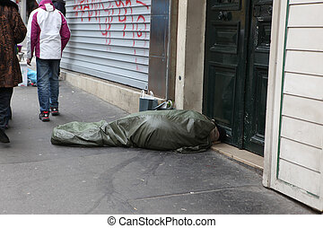PARIS - MAY 1 : Homeless man curled up under a plastic tarpaulin, asleep on the street, May 1, 2013 in Paris, France. Today, France has 130,000 homeless, and every day one of them dies