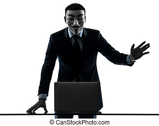 PARIS– OCTOBER 30 : one man dressed and masked as a member of Anonymous underground group member computing computer saluting on October 30, 2012 in Paris ,France