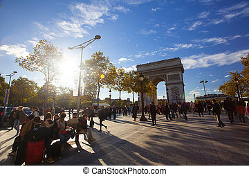 PARIS - OCTOBER 6, 2016: Tourists admire the beautiful architecture of the Triumphal Arch on Champs Elysees  in summer evening  boulevard in Paris, France