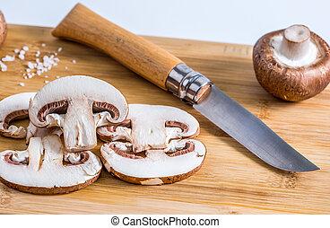 Parisian champignons, mushrooms on bamboo board. Side view.
