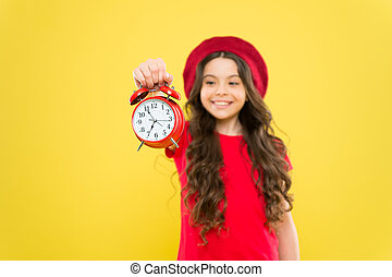 parisian child on yellow. beauty hairdresser. child with alarm clock. Timeless fashion. happy girl with long curly hair in beret. little girl in french style hat. time management. time to design