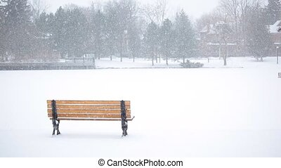 Park bench  - A park bench overlooks a snowy field.