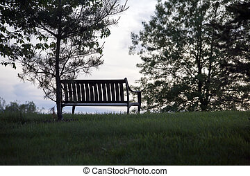 Park bench in silhouette at sunset