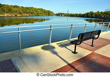 Park bench on pavilion overlooking river.