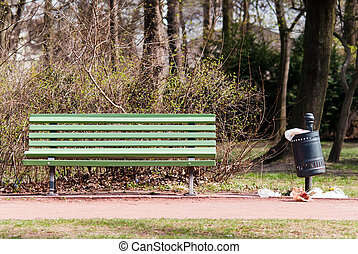 a green park-bench with a congested garbage can