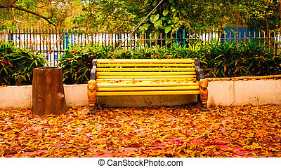Park bench with golden falken leaves in a community garden. Outdoor chair in a front or back yard lawn with Autumn leaf color Backgrounds. Japanese rock garden. Forest woodland environment.