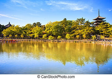 Park, pond and Toji temple pagoda in Nara city. Japan. -...
