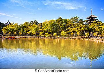 Park, pond and Toji temple pagoda in Nara city. Japan. -...