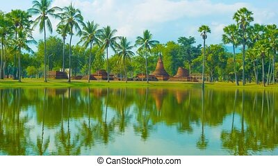 Park with a pond, palm trees and ruins of the temple