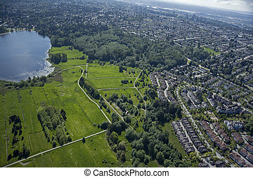 Park with lake and homes in Burnaby, British Columbia, Canada