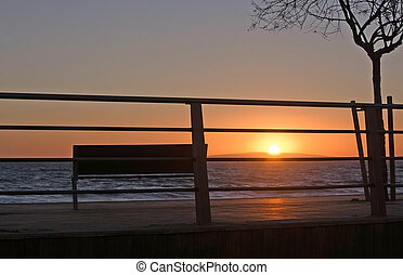 Parkbench and fence in Molinar at sunset on a winter...