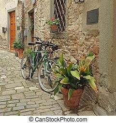 parked bikes on stone old tuscan street, borgo Montefioralle...