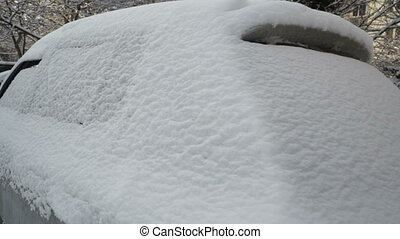 Parked car covered with snow in winter