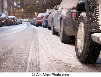 Low angle view of cars parked along a street at night in winter