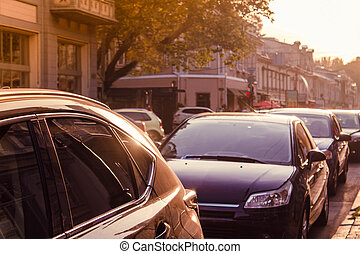 Parked cars standing on sunset street parking lot.
