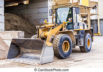 Parked pay loader near pile of dirt