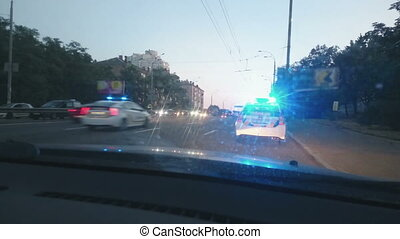 """Parked police car with blue roof lights twirling, emergency, city road accident"""