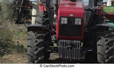 parked red tractor in the yard. front view of hood with wheels