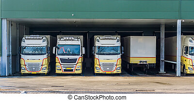 parked trucks at a docking station of a warehouse, logistics...