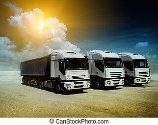 White trucks parked on a sand ground
