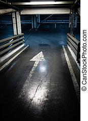 Parking garage in basement, underground interior, arrow sign