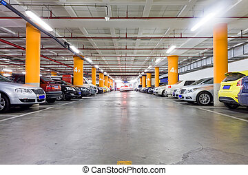 Parking garage, underground interior with a few parked cars...