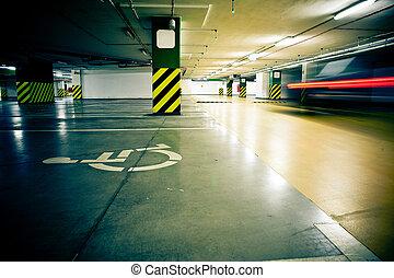 Parking garage, underground interior with car in motion blur