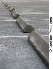 Concrete grey parking stoppers diagonal on empty parking lot.