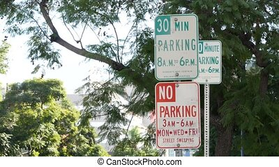 Parking lot sign as symbol of traffic difficulties and transportation issues in busy urban areas of USA. Public paid parking zone in downtown of San Diego, California. Limited space for cars in city.