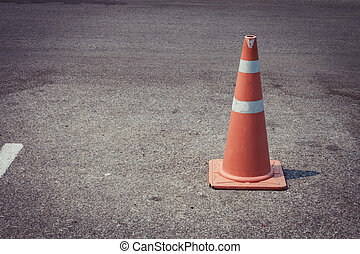 parking lot with traffic cone on street used warning sign on road