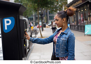 parking meter - young woman paying her parking ticket