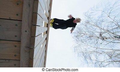 Parkour - a free runner blonde man jumps a flip at winter...