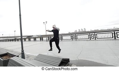 Parkour - a tracer blonde man jumps a flip outdoor,...