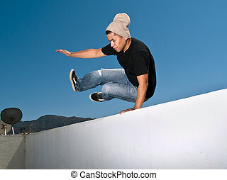 Parkour Freerunner - Parkour free runner jumping over a wall