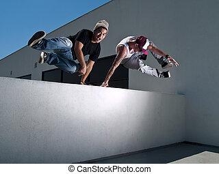 Parkour Freerunner - Parkour freerunners jumping over a wall